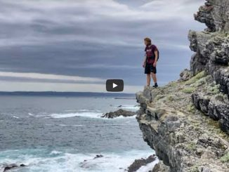 Hiker on rocky coast in Garden Route